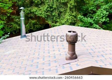 Modern chimneys on the roof of house - stock photo