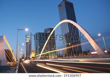 Modern city highway arc bridge night landscape of car light trails  - stock photo