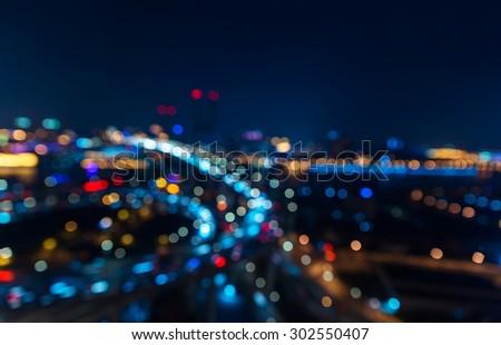 Modern city in bokeh. Transport road junction on the bridge. - stock photo