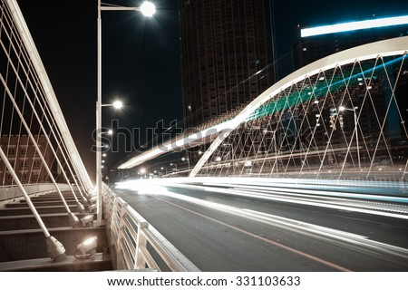 Modern city road arc ironbridge night landscape of car light trails in Tianjing - stock photo