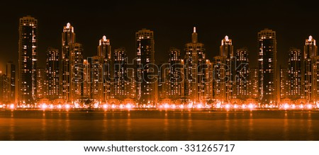 Modern city skyline at high with illuminated skyscrapers over water surface - stock photo