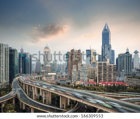 modern city skyline with elevated road junction and interchange overpass in shanghai at dusk  - stock photo
