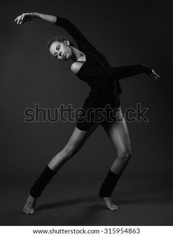 Modern classical dance theme: beautiful girl dancing sensual dance in a studio on a gray background, black and white photo - stock photo