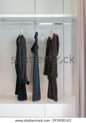modern closet with row of black dress hanging on coat hanger in wardrobe. - stock photo