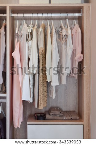 modern closet with row of dresses hanging in wooden wardrobe - stock photo
