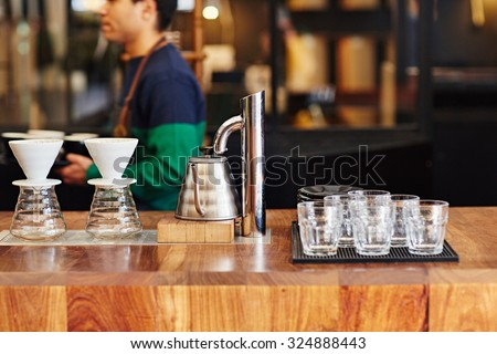 Modern coffee shop counter with glasses, coffee filters, and hot water kettle waiting for use on the wooden surface with a barista visible in the background - stock photo
