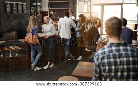 Modern coffee shop with customers standing at counter and sittin - stock photo