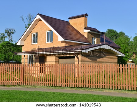 Modern colonial brick house in a beautiful summer day front yard surrounded by trees on a blue sky - stock photo