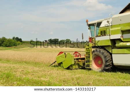 Modern combine harvester in the wheat field during harvesting - stock photo