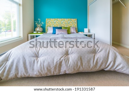 Modern comfortable, nicely decorated bedroom painted in blue Interior design. - stock photo