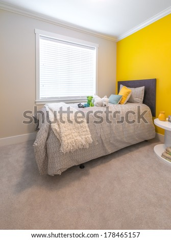 Modern comfortable, nicely decorated children bedroom painted in yellow. Interior design. - stock photo