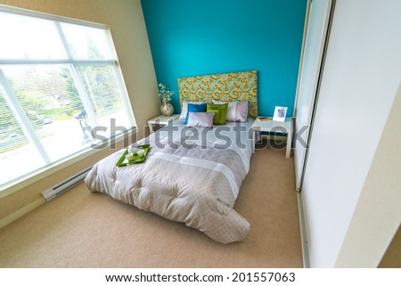 Modern comfortable, nicely decorated master, children bedroom painted in blue, and tray with the tea, coffee set on the bed. Interior design. - stock photo