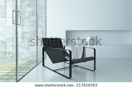 Modern comfortable recliner chair on a metal frame in a modern minimalist white living room interior in front of large glass windows and door leading to an outdoor patio - stock photo