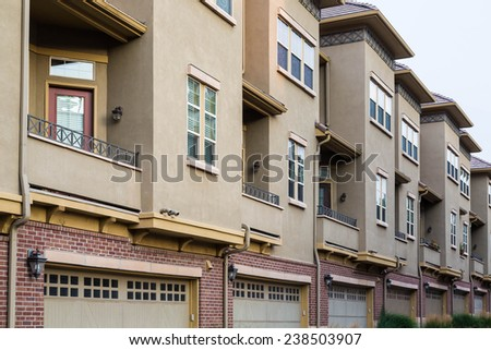Modern condominiums with closed drive under garages - stock photo