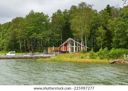 Modern country house on beach with pier and boat - stock photo