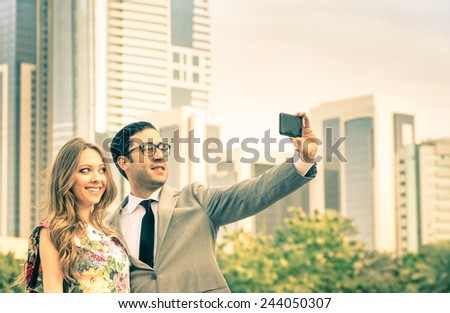 Modern couple taking a selfie at business center outdoors - Concept of love and interaction with new technologies and trends - Everyday life and positive feelings in urban financial district - stock photo