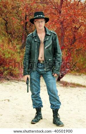 modern cowboy standing on sand, trees with red leaves on background - stock photo