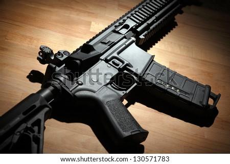 Modern custom AR-15 (M4A1) carbine on a wooden surface. Studio shot - stock photo