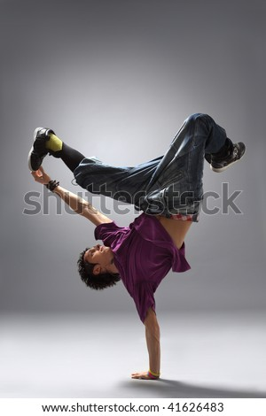 modern dancer poses in front of the gray background - stock photo