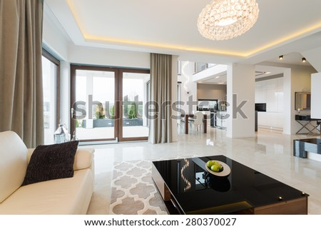 Modern decor of enormous bright lounge with fancy coffee table - stock photo