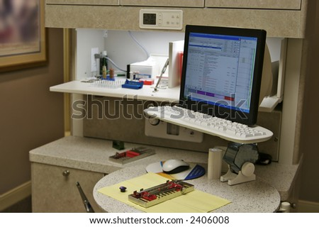 Modern dentist office with the are hygienist's station and equipment ready for a patient. The billing system is showing on the computer monitor. - stock photo