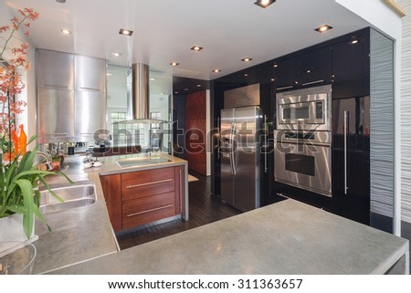 Modern design kitchen interior raw concrete counter tops and state of the art stainless steel appliances.  - stock photo