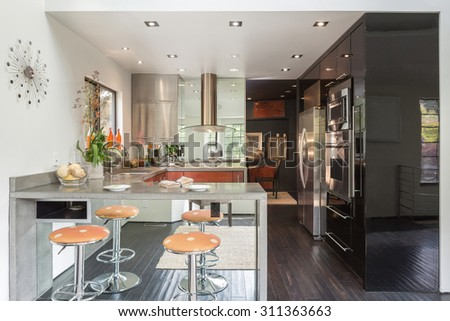Modern design kitchen interior with bar stools, mirrors, raw concrete counter tops and state of the art stainless steel appliances.  - stock photo