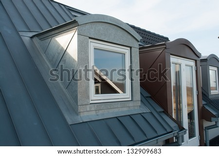 Modern design vertical roof window with black light metal covering - stock photo