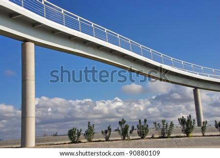 Modern designed white pedestrian bridge over a highway - stock photo