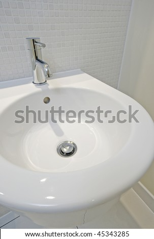 modern designer hand wash basin with chrome water mixer tap over - stock photo
