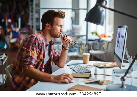 Modern designer sitting in front of computer in office - stock photo