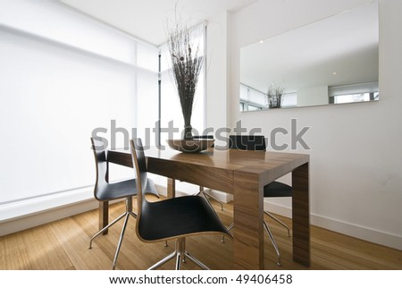 Modern dining area with wooden table and designer chairs - stock photo