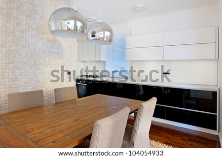 Modern dining room and black and white glossy kitchen - stock photo