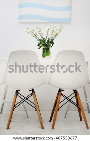 Modern dining room. White chairs and table with bouquet of flowers, abstract picture on the wall - stock photo