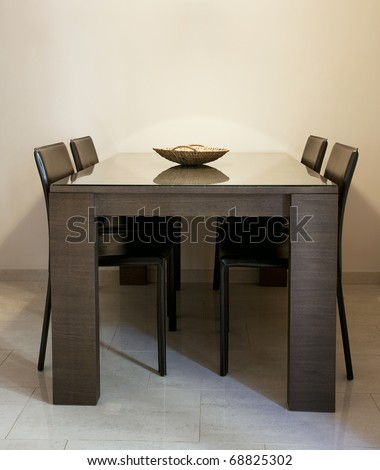 Modern dining room with brown chairs and a table with glass coating - stock photo