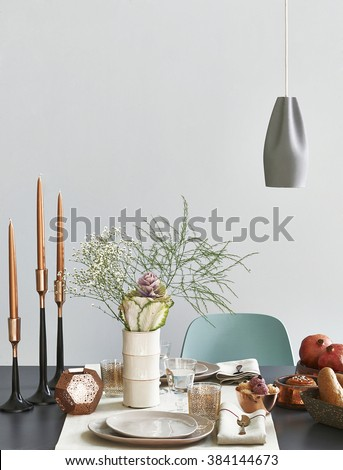 modern dining table setting green chair behind grey wall with vase of flower - stock photo