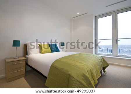 Modern double bedroom with king size bed and bedside tables - stock photo