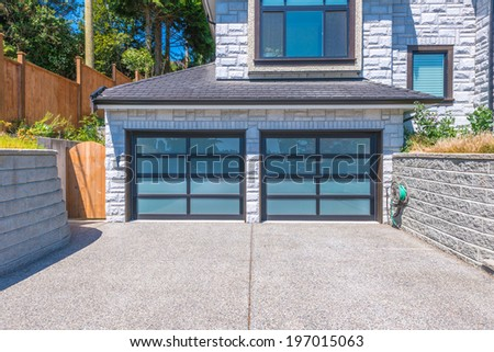 Modern double doors garage with wide long driveway.. - stock photo