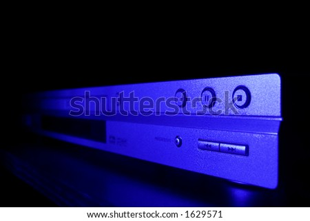 Modern DVD player lit by blue light and seen from an extreme angle. - stock photo