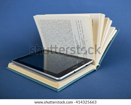 Modern ebook reader in traditional book  on a blue background - stock photo