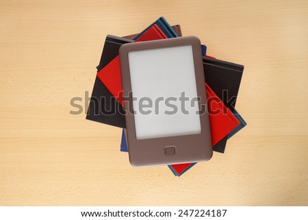modern ebook reader on top of pile of old books - stock photo