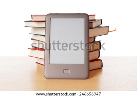 modern ebook reader stacked against pile of old books - stock photo
