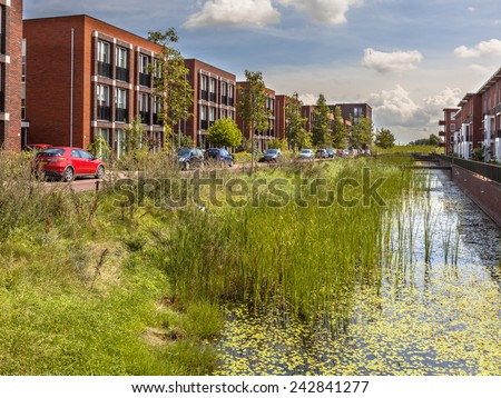 Modern ecological Street with middle class family apartments and eco friendly river bank in Wageningen city, Netherlands - stock photo