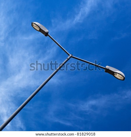 Modern electric street light pole over blue sky with clouds. - stock photo