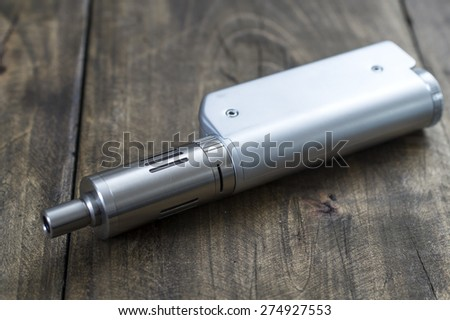 Modern electronic cigarette vaporize on the table,  close up - stock photo