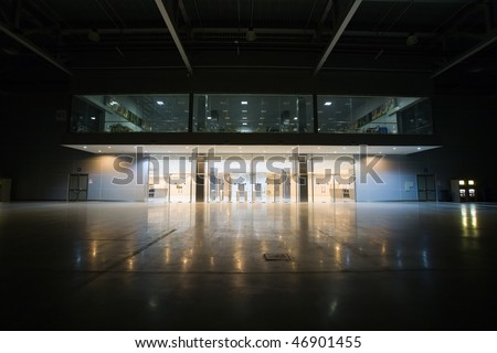 Modern empty storehouse with lights at far side - stock photo
