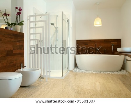 Modern en suite bathroom with free standing bath and travertine tiles. - stock photo