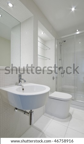 modern en-suite bathroom with glass slide door shower cabin - stock photo