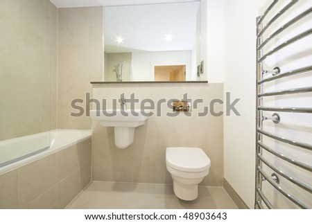 Modern en-suite bathroom with natural stone tiled walls - stock photo