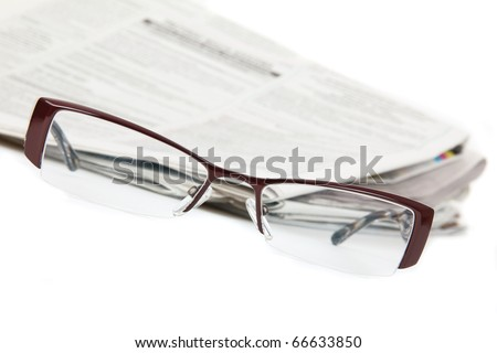 Modern eyeglasses and newspaper isolated on white - stock photo